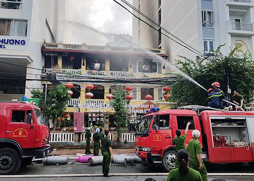 Cảnh sát phun nước khống chế đám cháy tại nhà hàng ở phố Tây Nha Trang. Ảnh: Xuân Ngọc