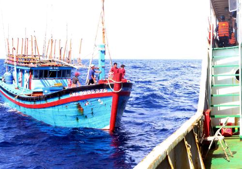 Tàu cá Quảng Ngãi đang được tàu hải quân Vùng 3 lai dắt vào bờ. Ảnh: C.K.