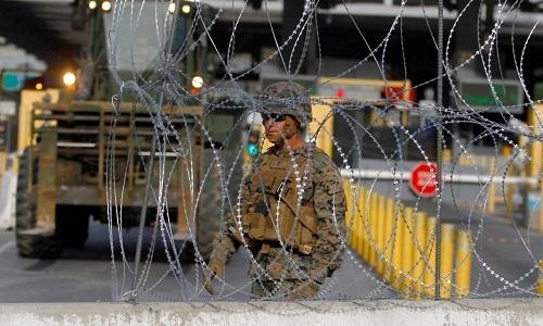 Lính Mỹ dựng hàng rào thép gai để ngăn đoàn người di cư tại biên giới Mexico. Ảnh: Reuters.