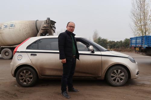 Cao đứng cạnh chiếc MG3 đã dùng 6 năm. Ảnh: Reuters/Yilei Sun