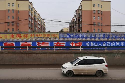 Bức tường ngăn cách khu dân cư và đường công cộng được lấp kín bằng quảng cáo của một đại lý ôtô địa phương ở Bình Đỉnh Sơn. Ảnh: Reuters/Yilei Sun