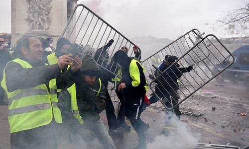 Người biểu tình xô đổ rào chắn do cảnh sát dựng lên trên đại lộ Champs-Élysées. Ảnh: AFP.