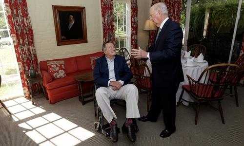Cựu tổng thống George H. W. Bush (ngồi xe lăn) và cựu ngoại trưởng James A. Baker III năm 2012. Ảnh: AP.