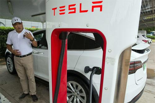 Trong bức ảnh chụp ngày 22/6, Shan Junhua nói về quyền riêng tư cạnh chiếc Tesla đang sạc pin ở Thượng Hải.