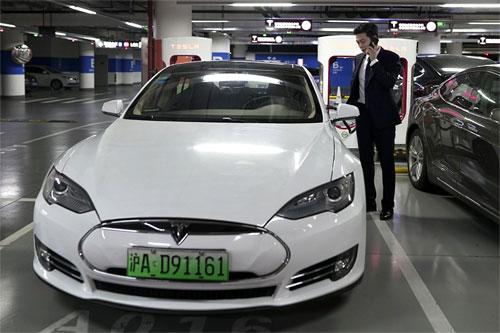 Một chủ xe Tesla đang đứng gọi điện cạnh mẫu xe điện thuộc thương hiệu Mỹ. Ảnh: AP.