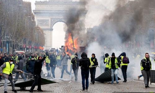 Người biểu tình tụ tập, đốt lửa trước Khải Hoàn Môn ở Paris, ngày 1/12. Ảnh: Time.