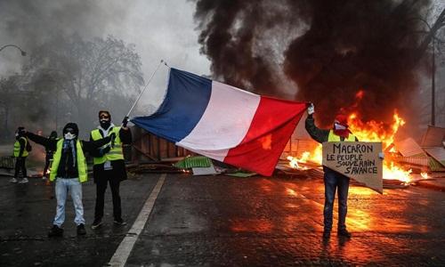Người biểu tình đốt rào chắn ở Paris hôm 2/12. Ảnh: AFP.