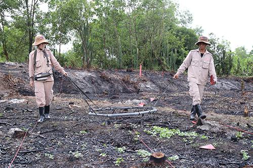 Nhân viên của một dự án phi chính phủ nước ngoài thực hiện dò tìm vật liệu nổ chiến tranh còn sót lại.Ảnh:Hoàng Táo