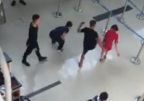 Nữ nhân viên sân bay bị nhóm thanh niên đánh vào đầu, đạp ngã tại sảnh ga đi. Ảnh cắt từ clip.
