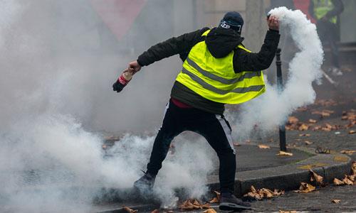 Một người biểu tình ném trả lựu đạn hơi cay về phía cảnh sát ở Paris hôm 1/12. Ảnh: Al Jazeera.