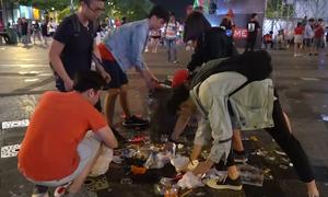 Nhiều bạn trẻ nán lại nhặt rác trên phố Nguyễn Huệ sau khi xem bóng đá