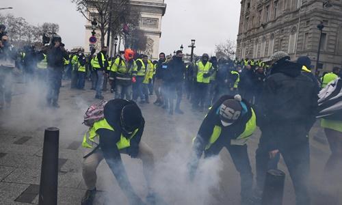 Hai người biểu tình trong phong trào áo vàng cầm đạn hơi cay. Ảnh: Sky News.