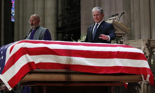Cựu tổng thống Bush (phải) bên cạnh quan tài cha. Ảnh: AFP.
