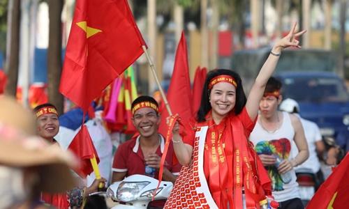Người bán các vật phẩm trang trí, cổ vũ đội tuyển Việt Nam trước trận đấu với Philippines ở sân vận động Mỹ Đình ngày 6/12. Ảnh: Ngọc Thành.