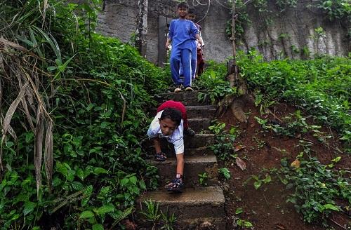Mukhlis bò đến trường trên địa hình xấu. Ảnh: Carters News