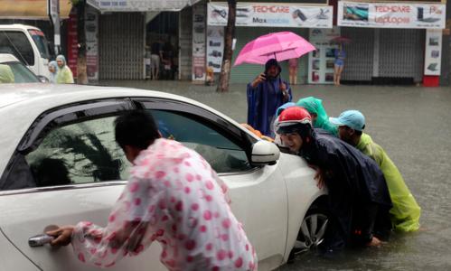 Hàng loạt ôtô xe máy bị hư hỏng khi phố biến thành sông. Ảnh: Nguyễn Đông.
