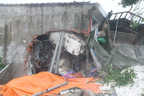 Một mảng tường của ki-ốt vật liệu xây dựng bị tông sập. Ảnh: Đức Hùng