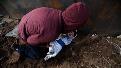 Bé trai Daniel được bố đưa qua lỗ đào dưới bức tường biên giới để vào Mỹ hôm 7/12. Ảnh: AP.