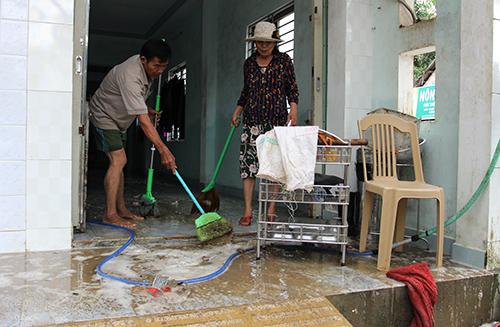 Ông Huỳnh Văn Hồi, ở phường Tân Thạnh, TP Tam Kỳcùng vợ đẩy bùn, lau chùi nhà sau khi nước rút. Ảnh:Đắc Thành.
