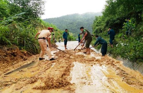 Công an huyện Ba Tơ khắc phục điểm sạt lở trên quốc lộ nối Quảng Ngãi với Kon Tum. Ảnh: Thạch Thảo.
