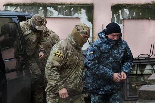 Đặc vụ Tổng  cục An ninh Liên bang Nga (FSB) hộ tống một thủy thủ Nga tới tòa án ở  Simferopol hôm 27/11. Ảnh: AFP.