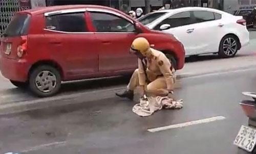 Cảnh thượng sỹ Hùng dùng dẻ lau dầu loang trên đường. Ảnh cắt từ clip.