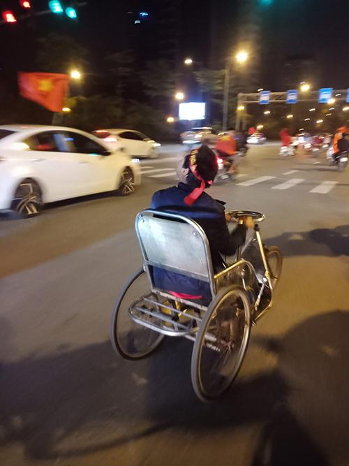 Một người khuyết tật cũng đẩy xe lăn đi ăn mừng. Ảnh: Nhân Hoàng