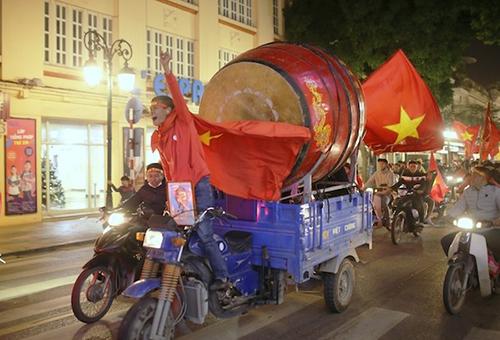 Thủ đô Hà Nội, nơi trận đấu diễn ra, người hâm mộ đổ xuống đường ngay khi tiếng còi kết thúc. Chiếc xe ba gác chở theo trống cỡ lớn để ăn mừng trên phố Tràng Tiền. Ảnh: Tất Định