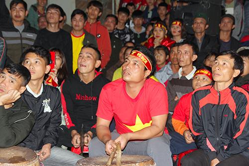 Người dân tập trung trước cổng nhà Văn Đức xem trận chung kết lượt đi AFF Cup giữa Malaysia và Việt Nam. Ảnh: Hải Bình