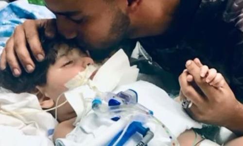 Bố của bé Abdullah hôn con trai trên giường bệnh. Ảnh: CBS.