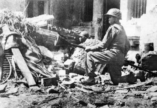 Chiến sĩ vệ quốc quân cảm tử ôm bom ba càng chặn xe tăng Pháp trên phố Hà Nội năm 1946. Ảnh tư liệu.