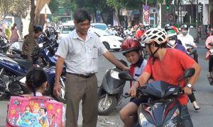 Thầy hiệu trưởng cúi đầu chào đón học sinh ở Sài Gòn