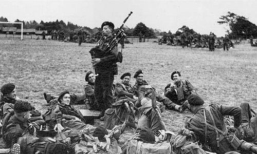 Bill Millin (đứng) chơi kèn túi cho các đồng đội trước trận đánh. Ảnh: War History.