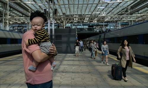 Một người đàn ông bế trẻ ở ga tàu Seoul hôm 22/9/2018. Ảnh: AFP.