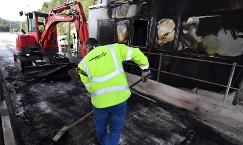 Công nhân công ty Vinci Autoroutes dọn dẹp đống đổ nát tại một trạm thu phí bị người biểu tình đốt phá. Ảnh: AFP.
