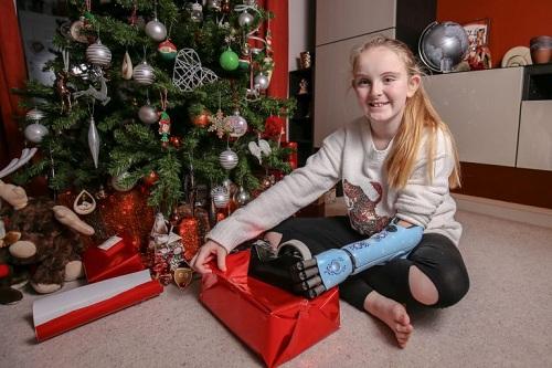 Evie tập gói quà Giáng sinh cho gia đình bằng cánh tay mới. Ảnh: Mercury Press
