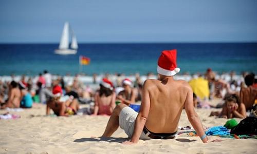 Người dân Australia đội mũ ông già Noel tắm nắng trên bãi biển. Ảnh: AAP.