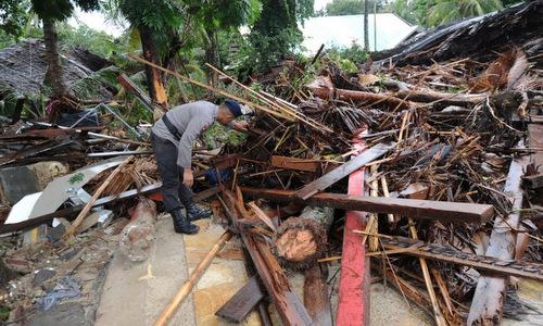 Một sĩ quan cảnh sát tìm nạn nhân trong đống đổ nát ở đảo Java sáng 24/12. Ảnh: AFP.