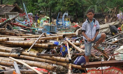 Một thiếu niên đứng trên đống đổ nát ở tây đảo Java chiều 24/12. Ảnh: AFP.
