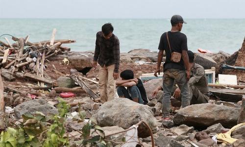 Người sống sót tìm kiếm nạn nhân và đồ đạc trong các đống đổ nát chiều 23/12. Ảnh:AFP.