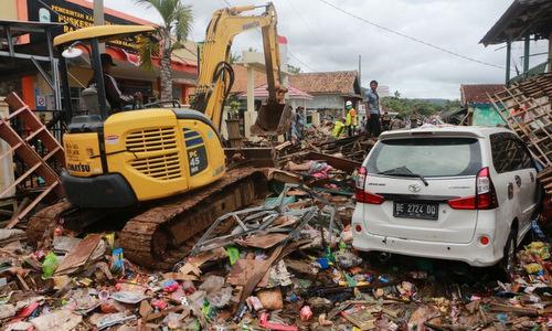 Lực lượng cứu hộ Indonesia dùng máy xúc đào bới các đống đổ nátsáng 24/12. Ảnh: AFP.
