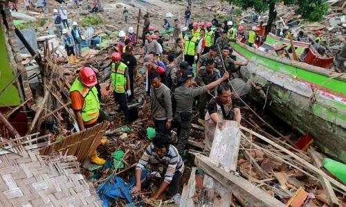 Lực lượng cứu hộ tìm kiếm người sống sót trong đống đổ nát chiều 23/12. Ảnh: AFP.