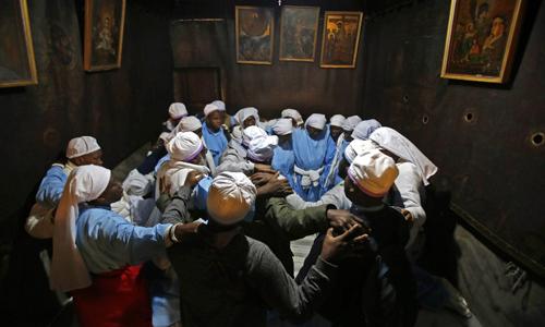 Những người hành hương từ Nigeria cầu nguyện trong hang đá tại Bethlehem, được cho là nơi Chúa Jesus ra đời. Ảnh: AFP.