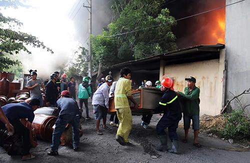 Cảnh sát cứu hỏa di dời đồ đạc trong một nhà xưởng bốc cháy ra ngoài. Ảnh: Phước Tuấn.