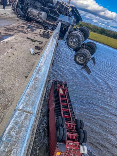 Phần đầu xe tải vắt ngang thành cầu, trong khi container lật ngửa và nằm dưới sông. Ảnh: Twitter.