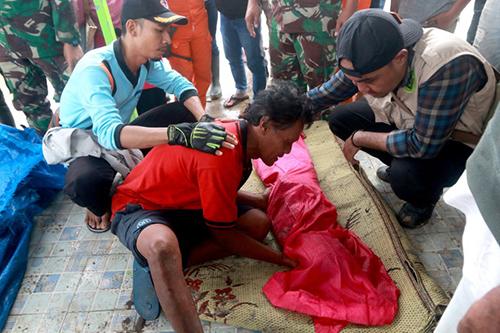 Một người đàn ông khóc bên thi thể của con thiệt mạng do sóng thần ở Nam Sumatra, Indonesia. Ảnh: AFP