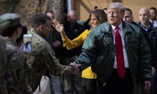 Trump (cà vạt đỏ) thăm căn cứ tại Iraq. Ảnh: AFP.