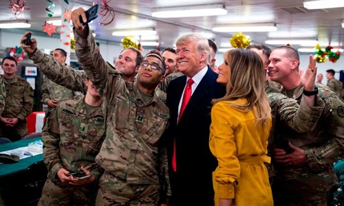 Tổng thống Trump và Đệ nhất phu nhân Melania chụp ảnh lưu niệm cùng các binh sĩ tại căn cứ không quân Al Asad hôm 26/2. Ảnh: AFP.
