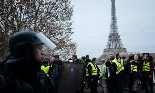 Những người biểu tình Áo vàng bị cảnh sát chống bạo động chặn lại trên cầu Hakeim ở Paris ngày 29/12. Ảnh: AP.