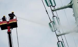 Công nhân phun nước rửa đường dây điện cao thế ở Sài Gòn